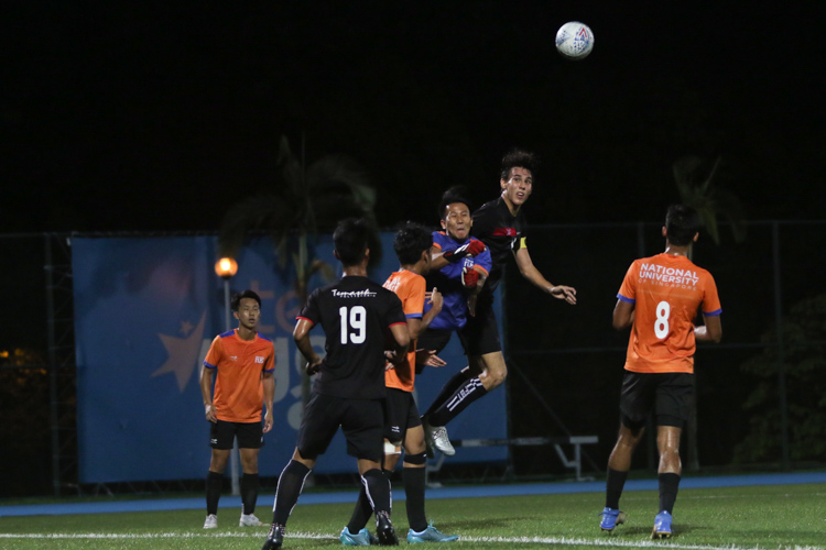 NUS keeper Teo Guan Kai Gabriel (#18) punches the ball clear in an aerial contest with TP captain Mahler Jacob William (#17). TP edge out NUS 2-1 to claim IVP Football championship. (Photo 3 © Clara Lau/Red Sports)