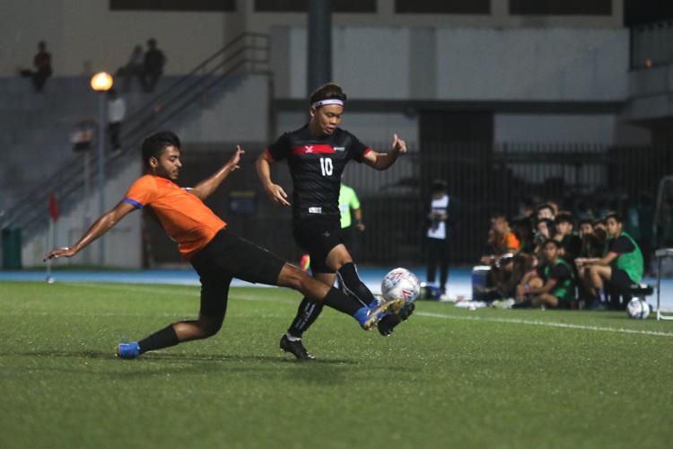 Shamir Robinson Panackal Sebastian (NUS #8) puts in a sliding tackle to dispossess Justin Hui Yong Kang (TP #10). TP edge out NUS 2-1 to claim IVP Football championship. (Photo 5 © Clara Lau/Red Sports)